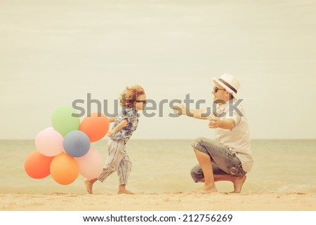 Father and son with balloons playing on the beach at the day time. Concept of friendly family. - stock photo