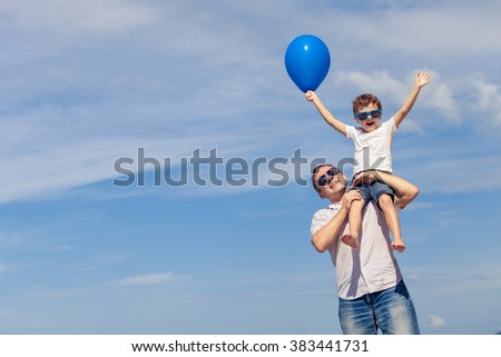 Father and son with blue balloon playing on the beach at the day time. Concept of friendly family. - stock photo
