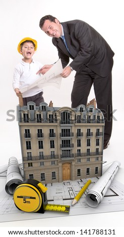 Father and son with blueprints and a building - stock photo