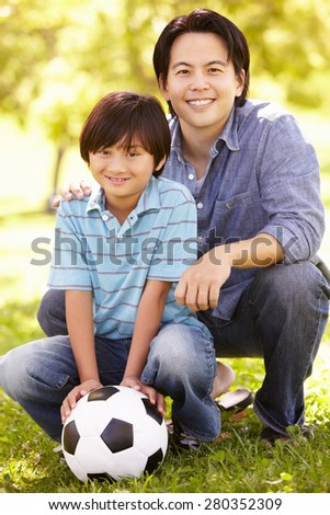 Father and son with football - stock photo