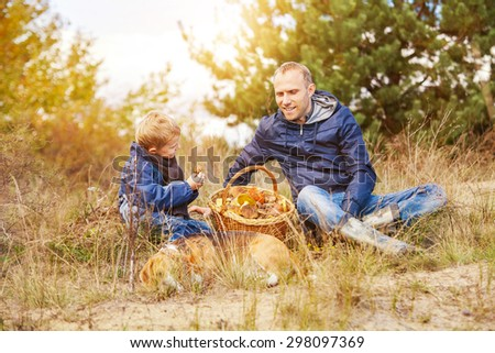 Father and son with full basket of mushrooms rest  in forest - stock photo