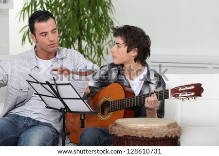 Father and son with guitar - stock photo