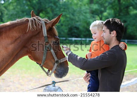 father and son with horse - stock photo