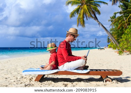 father and son with laptop on beach vacation - stock photo