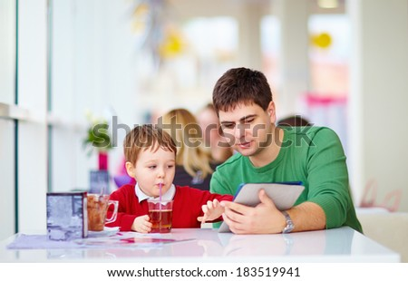 father and son with tablet in colorful cafe - stock photo