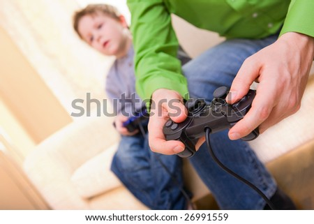 Father and son with video game controllers - stock photo