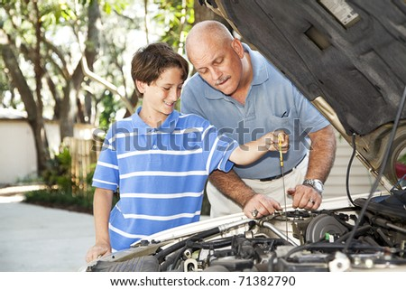 Father and son working on the car together.  The son is checking the oil. - stock photo