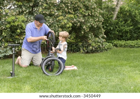 Father and Son, 6 year old boy, are spending quality time together fixing a bike. They are in a backyard sitting on grass, trees behind them with a bicycle between them