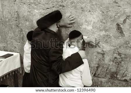Father and sons pray in the western wall in Jerusalem. - stock photo