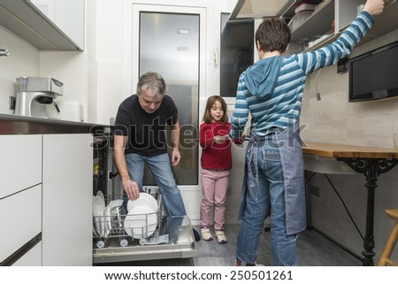 Father and sons together emptying the dishwasher - stock photo
