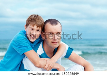 father and sons walking on beach, outdoor - stock photo