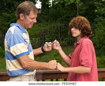 Father and teen son double fist-bumping - stock photo
