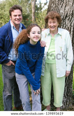 Father and teenage daughter pose for an outdoor portrait with a lovely senior grandmother.
