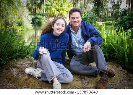 Father and teenage daughter spending Fathers Day in a beautiful outdoor location, hiking or camping. - stock photo