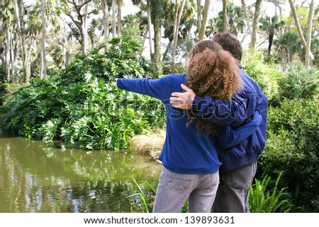 Father and teenage daughter vacationing in Florida and visiting a cypress swamp nature preserve. - stock photo