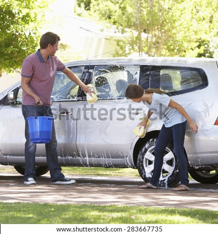 Father And Teenage Daughter Washing Car Together - stock photo
