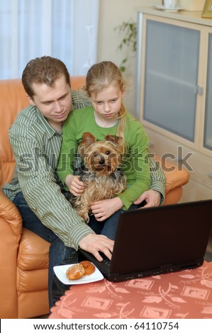 Father and teenage daughter with small dog looking into a portable computer at home. - stock photo