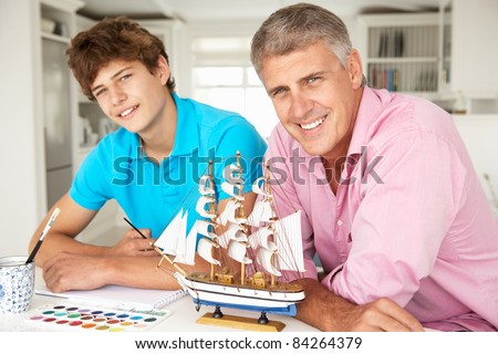 Father and teenage son model making and painting - stock photo