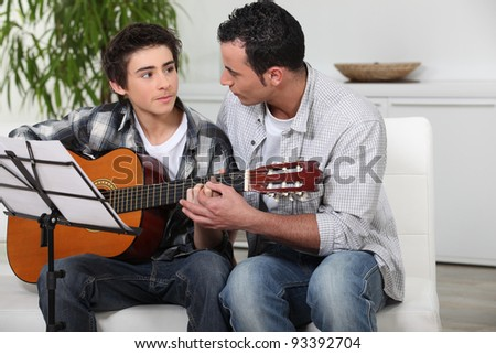 father and teenage son playing the guitar - stock photo