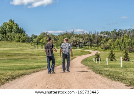 Father and teenage son spending quality time together talking and walking down a gravel  gravel path with lots of green grass and trees in the summer time. - stock photo