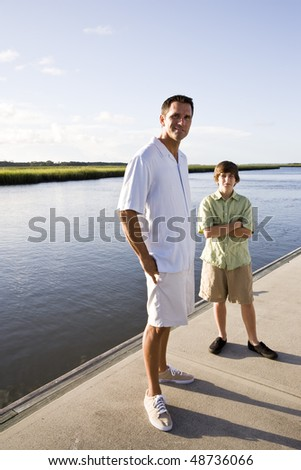 Father and teenage son standing on dock by water on sunny day - stock photo