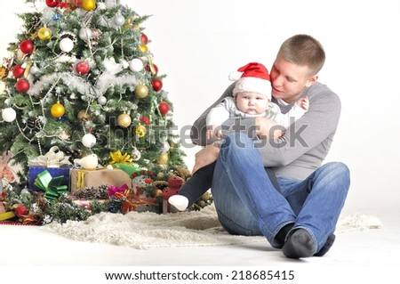 Father and their small child sits near Christmas tree - stock photo