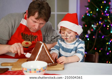 Father and toddler boy preparing a gingerbread cookie house at christmas time - stock photo