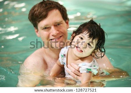 Father and toddler boy swimming in pool. Child has cerebral palsy.