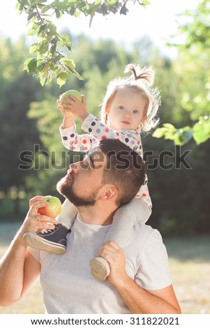 Father and toddler have fun with apple in garden