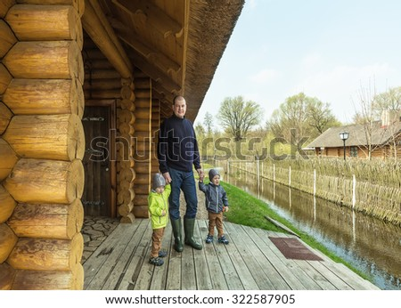 Father and twins on the threshold of wooden house, spring flood, Belarus, near Brest - stock photo