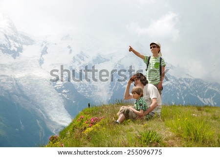 father and two boys look on mountains from the cliff edge - stock photo