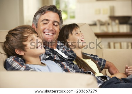 Father And Two Children Sitting On Sofa At Home Watching TV Together - stock photo