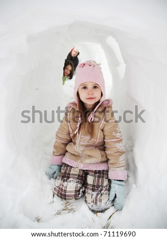 Father and two daughters playing in a snow fort tunnel - stock photo