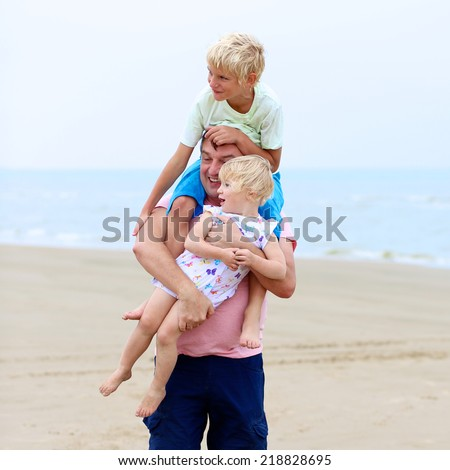 Father and two happy active children, teenage boy with his little sister, cute blonde toddler girl, playing on wide sandy beach at the sea - stock photo