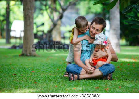 Father and two kids having fun outdoors at sunny summer day