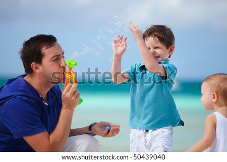 Father and two kids on tropical beach playing with soap bubbles. Focus on boy. - stock photo