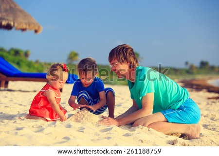 father and two kids playing with sand on summer beach - stock photo