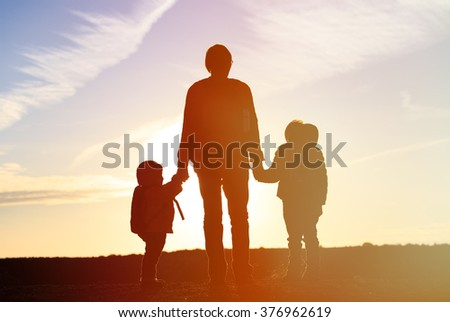 father and two kids travel at sunset