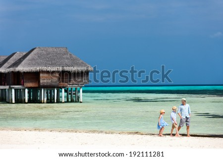 Father and two kids walking along a tropical beach enjoying summer vacation - stock photo
