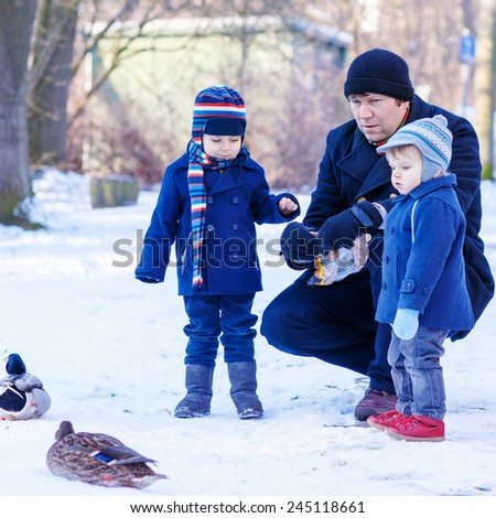 Father and two little siblings boys feeding ducks in winter. Family having fun together in city park. Leisure with kids in winter on cold sunny day, outdoors. - stock photo