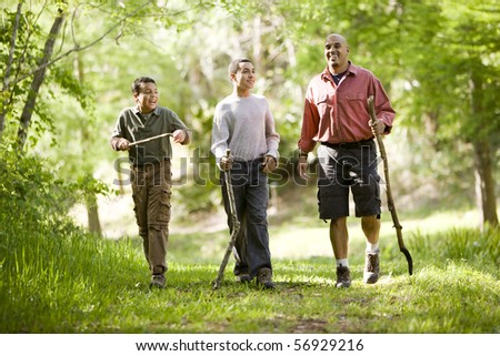 Father and two sons hiking on trail in woods and talking