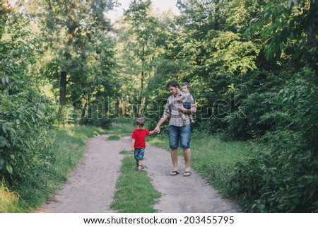 Father and two sons walking outdoors  - stock photo