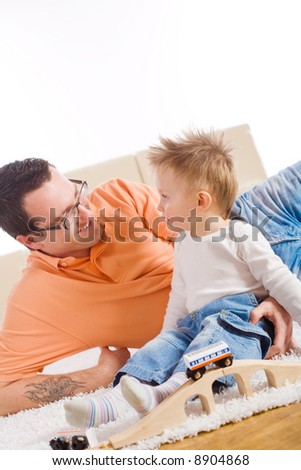 Father and two year old child playing together with wooden toy train. Sitting on floor at home, smiling. - stock photo