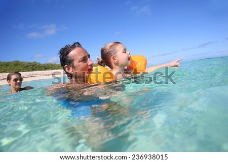 Father and 4-year-old girl bathing in the sea - stock photo