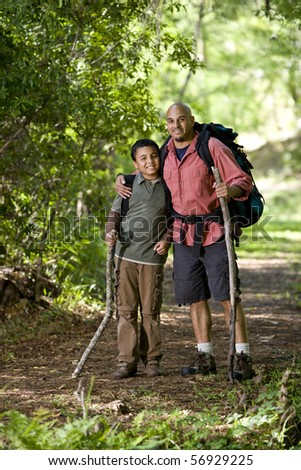 Father and 10 year old son hiking on trail in woods