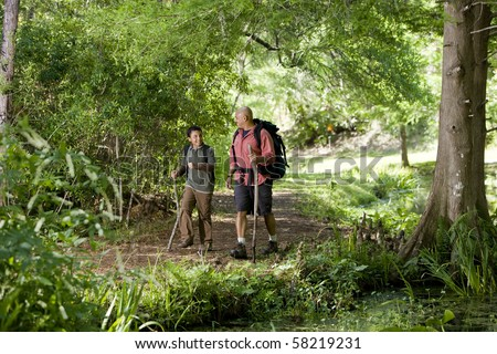Father and 10 year old son hiking on trail in woods and talking
