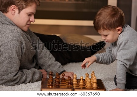 Father and 4 years old child playing chess at home in a cold winter day. - stock photo
