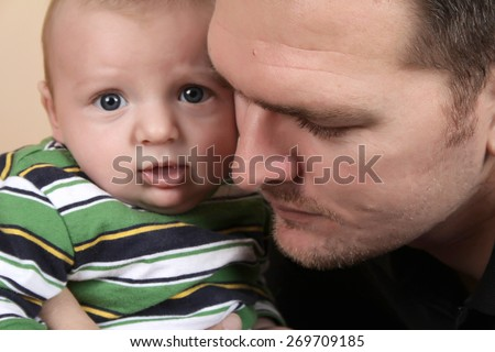 Father and young baby with faces close together - stock photo