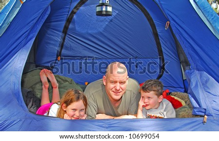 Father and young children in camping in dome tent - stock photo