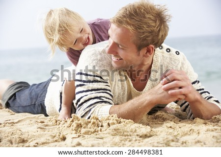 Father And Young Daughter Sitting On Beach Together - stock photo